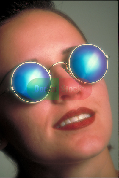 smiling young woman with sunglasses looking into bright light
