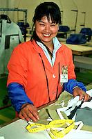 Bacau / Romania<br /> La Sonoma, industria tessile dove vengono prodotti capi di lusso per vari marchi importanti del 'Made in Italy', è un vero esempio di globalizzazione nel mondo del lavoro: fabbrica rumena, AD italiano, operai provenienti da Cina e Bangladesh.<br /> Nella la signora Fu Lihua, operaia cinese proveniente da Nanchino, 34 anni, madre di due figli rimasti in Cina.<br /> Sonoma textil factory in Bacau is an example of globalization: italian AD, romanian factory, workers from China and Bangladesh.  In the picture Mrs. Fu Lihua, working from Nanjing, 34 years old, mother of two children left in China.<br /> Photo Livio Senigalliesi