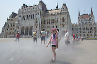People cool down in the summer heat by the water cloud of the humidifiers in front of the building of the Parliament in downtown Budapest, Hungary on July 19, 2015. ATTILA VOLGYI