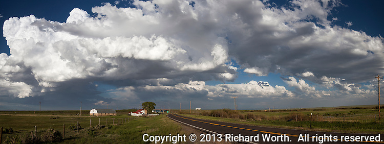 Huge white clouds float over a two-lane highway and a barn with farm house near a freeway overpass west of Laramie, Wyoming.