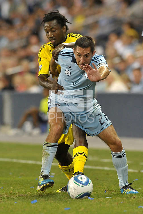 Sporting KC midfielder Davy Arnaud (22) holds off the challenge ffrom Columbus Crew midfielder Emmanuel Ekpo.