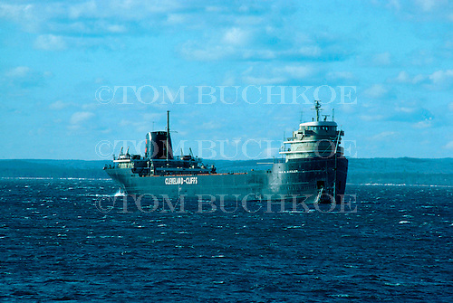 M/V Tom M Girdler, part of the Cleveland-Cliffs Iron Company fleet, approaches  Marquette Michigan's upper harbor on Lake Superior. Circa 1970's