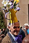 A man in the New York City Easter Parade wearing a hat made out of a bright yellow watering can and purple flowers