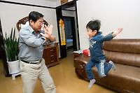 """Quan Husheng s'amuse à combattre son petit-fils Shen Xuanwu """"Gregoire"""" 5 ans, féru d'arts martiaux et de superhéros, dans leur appartement de Yanji, province de Jilin, en Chine, le 7 septembre 2009. Photo par Lucas Schifres/Pictobank"""