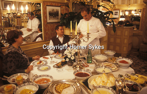 Paul Bocuse in Lyon France portrait signing menus in his restaurant. 1980s