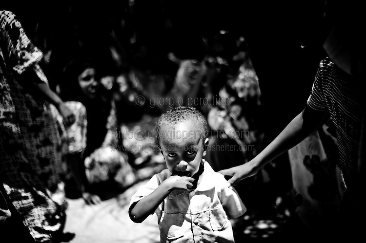 Malnutrition in the Horn of Africa.<br /> <br /> A young boy puts his hand into the mouth at the State House Refugee Camp of Hargeisa, the capital city of Somaliland in the Horn of Africa.<br /> The Northern region of former Somalia Republic reached its independence from the southern part in 1988 after a long period of civil war, but it is not actually recognized by any international country and community.     <br /> Hargeisa, Somaliland - 8th Aug 2011<br /> © Giorgio Perottino