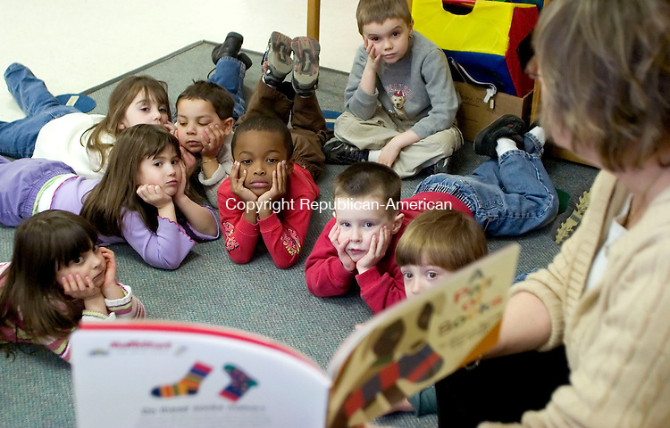 TORRINGTON, CT- 07 MARCH 07- 030707JT06- <br /> From left to right, pre-schoolers Sierra Eaton, ???????????(coming), Samantha Beardsley, Dadrian Moore, Christian Estafani, Skyler Cornett, Jacob Regner, and Jamin Stinson look at a book being read aloud by Cheryl Harrison Wednesday at Torrington Child Care, which is one of four accredited pre-school programs in the city.<br /> Josalee Thrift Republican-American