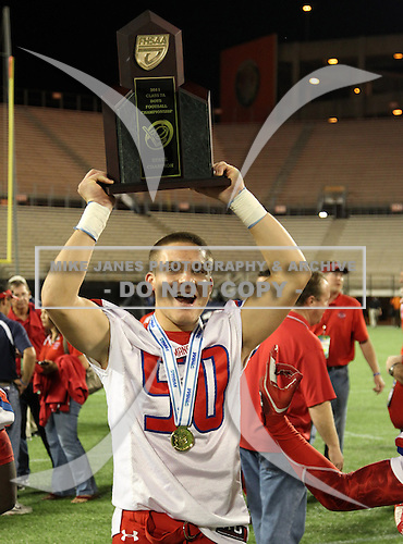 Manatee Hurricanes linebacker Alex Bernhardt #50 hoists the Championship trophy after the Florida High School Athletic Association 7A Championship Game at Florida's Citrus Bowl on December 16, 2011 in Orlando, Florida.  Manatee defeated First Coast 40-0.  (Photo By Mike Janes Photography)