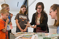 """NWA Democrat-Gazette/CHARLIE KAIJO Levi Sheridan, 7 (from left), Owen Sheridan 11, Abby Sheridan 16 and Karla Sheridan of Owasso, Okla. show Leana Fisher, artist from Fayetteville, flower art in the """"Create with an Artist"""" class, Friday, March 23, 2018 at Crystal Bridges Museum of Modern American Art in Bentonville. <br /><br />The museum offered free artmarking, acitivities and performances for Spring Break."""