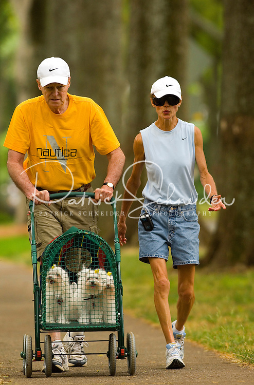 An elderly couple take their dogs for a walk in a converted stroller along Queens Road West in the Myers Park neighborhood in Charlotte, NC. Myers Park is one of the premier neighborhoods in North America and known for its large canopy of trees.