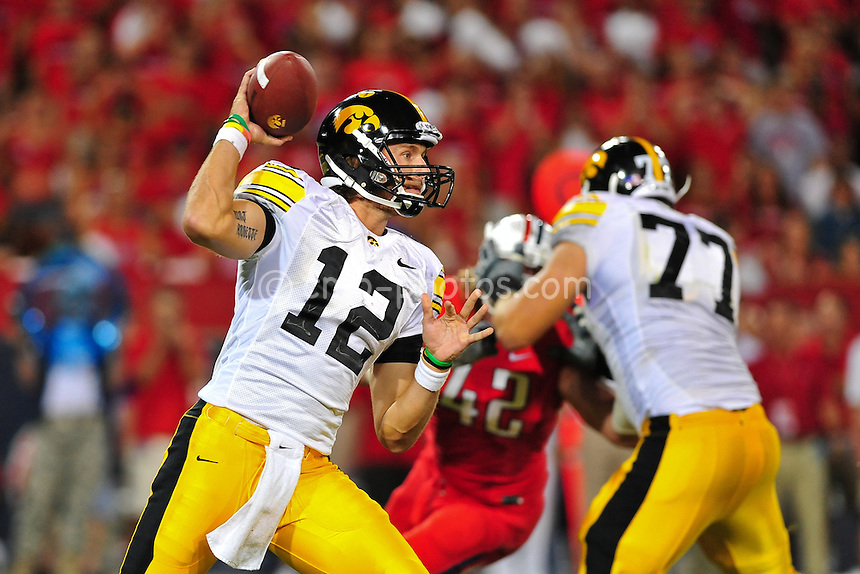 Sept 18, 2010; Tucson, AZ, USA; Iowa Hawkeyes quarterback Ricky Stanzi (12) pump fakes while dropping back to pass in the 3rd quarter of a game against the Arizona Wildcats at Arizona Stadium.  Arizona won the game 34-27.