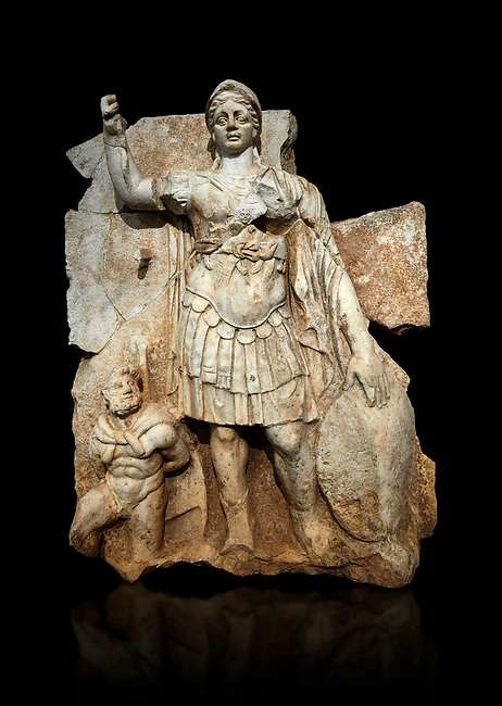Roman Sebasteion relief  sculpture of Roma armed, Aphrodisias Museum, Aphrodisias, Turkey.   Against a black background.<br /> <br /> Roma is equipped with a spear, helmet, round shield and imperial style armour. Blow crouches a naked bearded prisoner, with hands tied behind his back and a skin knotted around his neck. He turns to look up at Roma