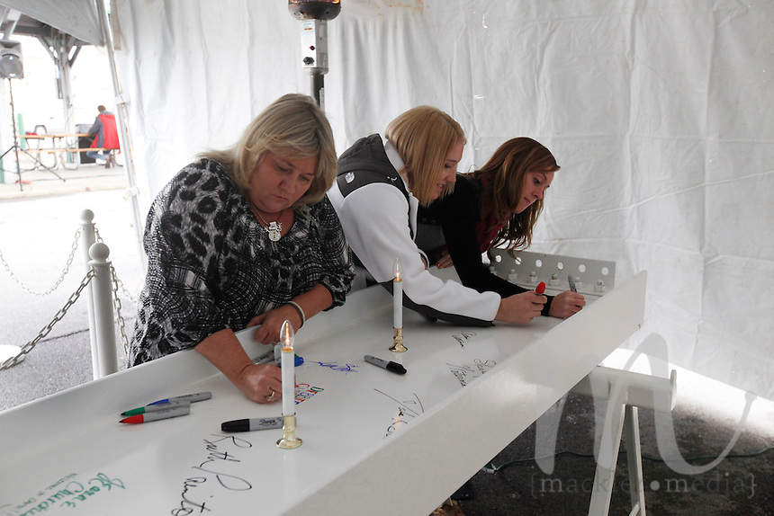 Debbie Clarke, Nicholle Hinkle and Kacie Broemmelsick, from left,  sign the steel beam that will be added to the Isle of Capri in the final stages of construction during Isle Casino Cape Girardeau's beam signing event held on Thursday, Dec. 15, 2011 in the parking lot across from Hutson's Fine Furniture in Cape Girardeau, Mo. Traditionally, the last piece of steel placed during construction is signed for good luck.