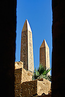 The two Obelisks of Queen Hatshepsut viewed between columns of the Hypostyle Hall, Temple of Karnak located at modern day Luxor, or ancient Thebes, Egypt