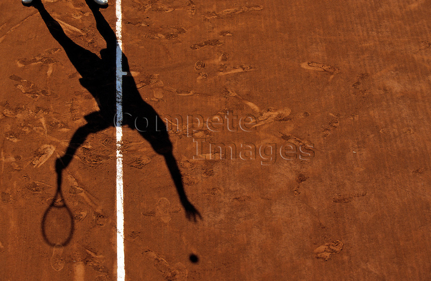 Shadow of a tennis player on a clay court