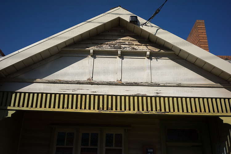 Old wooden house with peeling paint in bright sunlight