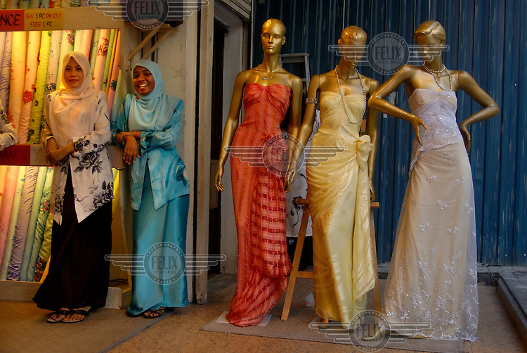 Sales assistants standing at the entry to a women's clothing shop, next to models displaying dresses, on Jalan Tunku Abdul Rahman.