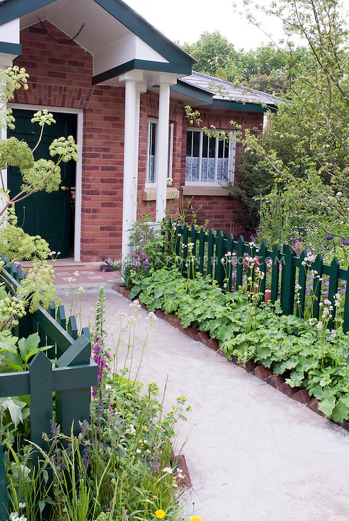 Front entry garden of brick house with green picket fence, green front door and trim, groundcover Alchemilla mollis starting to bloom, herbs angelica, spring, flowers and trees, front path walkway curb appeal. Mixture of edibles with oranmentals
