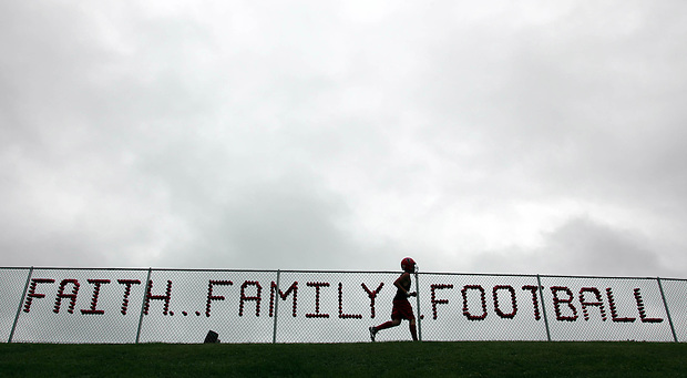 An Aplington-Parkersburg football player runs laps along a fenceline bearing a message before the team's practice.