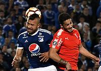 BOGOTÁ - COLOMBIA, 17-05-2018: Andrés Cadavid (Izq.) jugador de Millonarios (COL), salta a cabecear el balón con Martín Benítez (Der.) jugador de Club Atlético Independiente (ARG), durante partido entre Millonarios (COL) y Club Atlético Independiente (ARG), durante partido entre Millonarios (COL) y Club Atlético Independiente (ARG), de la fase de grupos, grupo G, fecha 5 de la Copa Conmebol Libertadores 2018, en el estadio Nemesio Camacho El Campin, de la ciudad de Bogota. / Andrés Cadavid (L) player of Millonarios (COL), jumps to head the ball with Martín Benítez (R) player of Club Atlético Independiente (ARG), during a match between Millonarios (COL) and Club Atletico Independiente (ARG), of the group stage, group G, 5th date for the Conmebol Copa Libertadores 2018 in the Nemesio Camacho El Campin stadium in Bogota city. VizzorImage / Luis Ramirez / Staff.