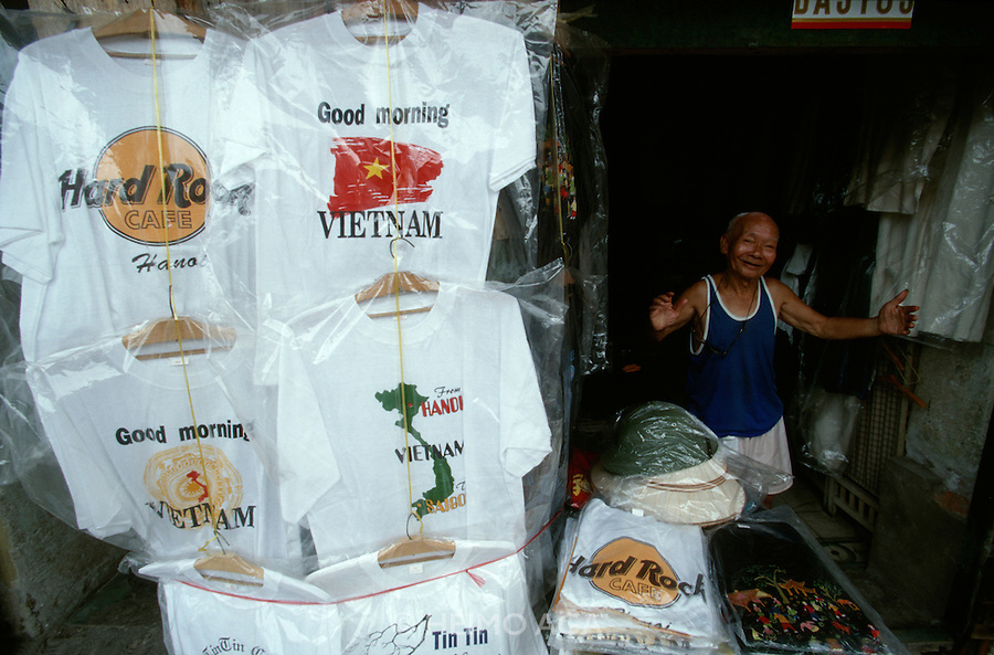 "Old man selling souvenir t-shirts, one of them with the inscription ""Good Morning, Vietnam"" after the blockbuster movie with Robin Williams."