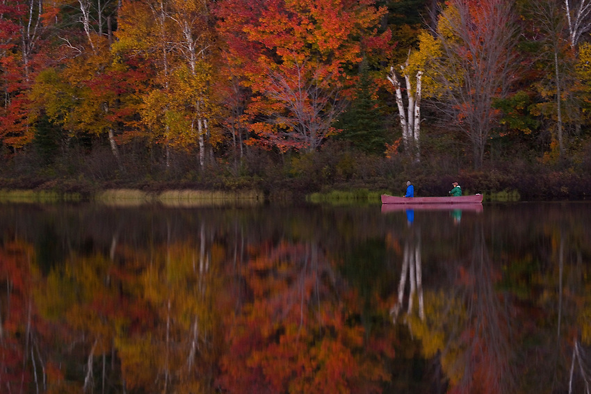 A pair of canoeists paddle through the reflection of trees with fall foliage on Harlow Lake near Marquette Michigan in autumn.