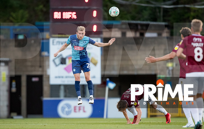 Jason McCarthy of Wycombe Wanderers clears from Dean Bowditch of Northampton Town during the Carabao Cup match between Wycombe Wanderers and Northampton Town at Adams Park, High Wycombe, England on 14 August 2018. Photo by Andy Rowland.