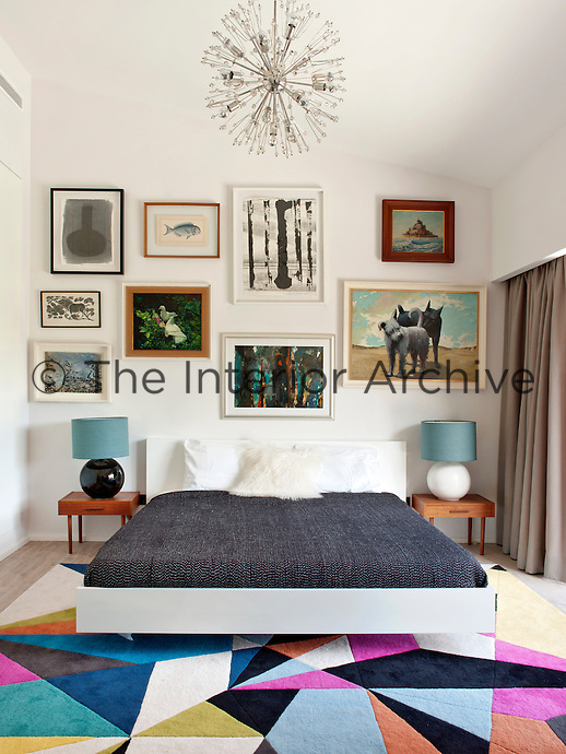 A bold geometric 'Americo' rug by Carpet Diem injects colour into the guest bedroom. Which has an eclectic collection of paintings hanging on the wall above the bed and a 1970s 'Sputnik' chandelier