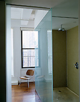 This shower is divided by a wall of glass and the wet area floor is of concrete while a timber floor covers the rest of the area