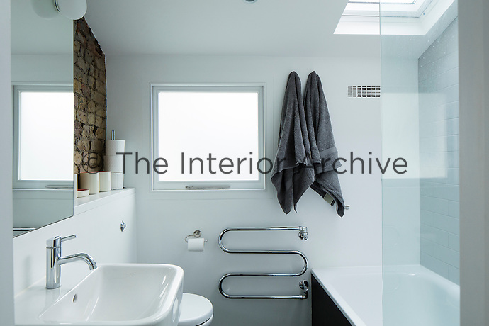 A Victorian home has been given a modernist aesthetic. The modern bathroom is clean and white whilst the exposed original brickwork lends a rustic touch.