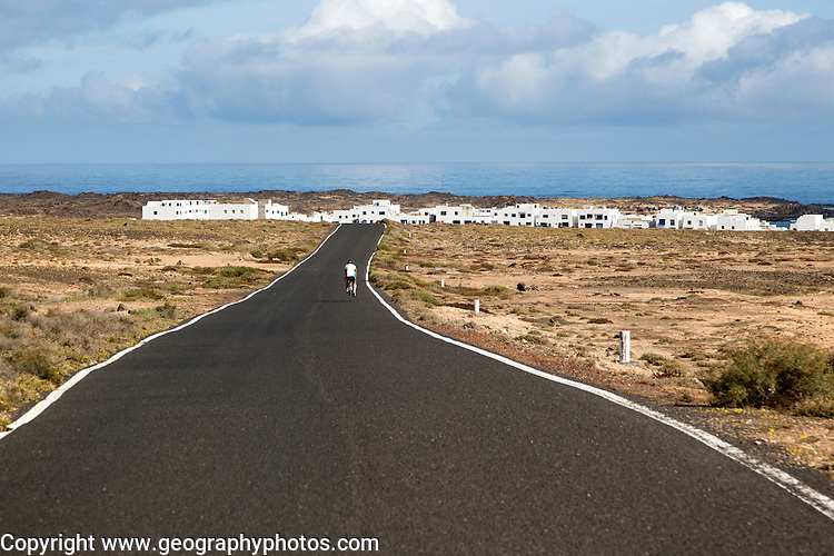 Cyclist on road approaching Caleta de Caballo village, Lanzarote, Canary islands, Spain