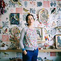 A portrait of artist, Nathalie Lété standing in front of a feature wall of hand painted tiles