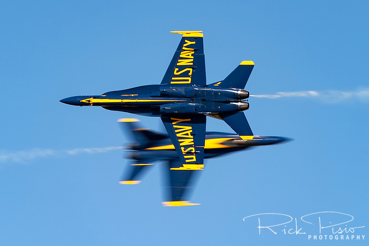 The United States Navy Blue Angel's Lead Solo and Opposing Solo pass each other at show center during the 2004 Lemoore Naval Air Station Airshow. With a closure rate of nearly 1200 mph split second accuracy and precision is required by the pilots in order to cross at the pre-determined point on the flight line.