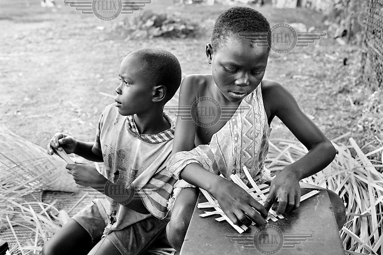 Two young boys who live on the street with their AIDS-sick mother in Kampala, Uganda, weave baskets on April 21, 2001.More than 13 million African children have been orphaned by the the AIDS pandemic. Worldwide, more than 20 million people have died since the first cases of AIDS were identified in 1981.