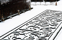 An ornate maze-like ornamental box hedge stands in relief against the snow-covered garden