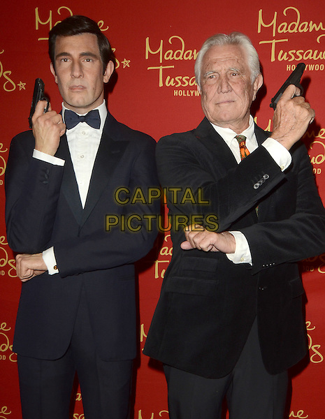 HOLLYWOOD, CA - DECEMBER 15: George Lazenby poses with his wax figure at the unveiling of six James Bond wax figures at Madame Tussauds on December 15, 2015 in Hollywood, California. <br /> CAP/MPI/DE<br /> &copy;DE//MPI/Capital Pictures