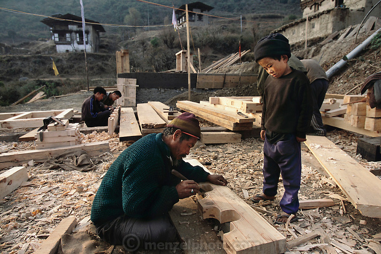 Nalim and Namgay's grandson, Geltshin, watches a wood worker cutting traditional shapes into a piece of wood for a new Bhutanese house. The carpenters, from another village, have set up camp and live at the work site while they do the woodwork for a new house in the village of Shingkhey, Bhutan. Traditional three-story houses built of rammed earth dot the hillside village of Shingkhey, Bhutan. Nalim and Namgay's neighbor is building a new house for his family directly in front of his old one. Carpenters from another village build the wooden structures such as doorways, rafters, windows, and lintels. Villagers from each family come to help pound the dirt into wooden forms day after day, creating the walls of the earthen house. From coverage of revisit to Material World Project family in Bhutan, 2001.