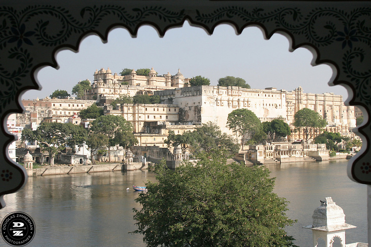 "View of the City Palace of Udaipur, Rajasthan, India across Pichola Lake through an arch.  Udaipur sits in a valley surrounded by the Aravalli hills, and at its center is the Pichola Lake.  The scenic city has been described as ""the most romantic spot on the continent of India"" (by Colonel James Tod).  Photograph by Douglas ZImmerman"