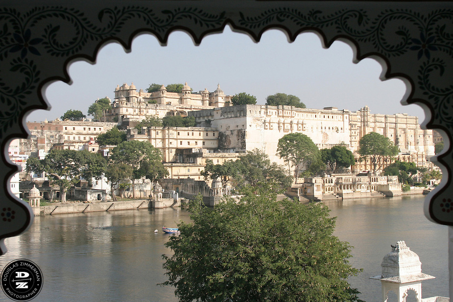 """View of the City Palace of Udaipur, Rajasthan, India across Pichola Lake through an arch.  Udaipur sits in a valley surrounded by the Aravalli hills, and at its center is the Pichola Lake.  The scenic city has been described as """"the most romantic spot on the continent of India"""" (by Colonel James Tod).  Photograph by Douglas ZImmerman"""