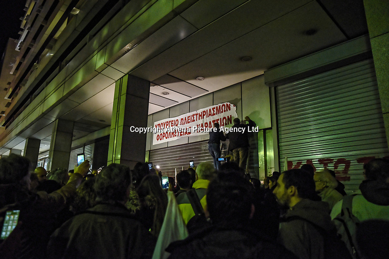 """Protesters from the communist-affiliated trade union PAME place a banner which reads """"Ministry of foreclosures and tax thieves"""" at the entrance of the Finance Ministry during a demonstration against property foreclosure auctions in Athens, Greece. Wednesday 21 February, 2018."""