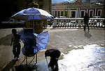 Children clean the ground near their market-booth in the main square of Xela, Guatemala