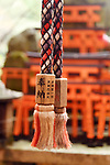 Rope of a Suzu, Japanese Shinto shrine bell with Offering written on it at Fushimi Inari shrine in Kyoto, Japan.