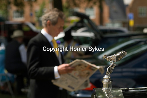 Horse racing at Royal Ascot, Berkshire, England. 2006. Studying the racing form. Number 1 car park. Rolls Royce car.
