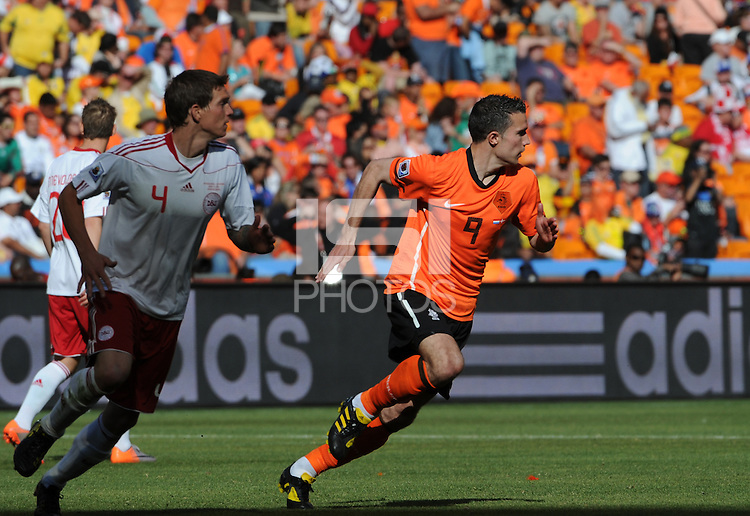 Holland's Robin Van Persie runs to space, trailed by Denmark's Daniel Agger. Holland defeated Denmark, 2-0, June 14th, at Soccer City in the opening match of Group E of the 2010 FIFA World Cup.
