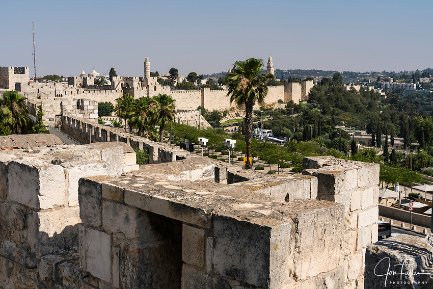 The city wall of Jerusalem near the Jaffa Gate with the minaret of the Tower of David or the Citadel in the center.  At right is the bell tower of the Dormition Abbey on Mount Zion, outside the walls.  The Old City of Jerusalem and its Walls is a UNESCO World Heritage Site.