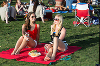Two beautiful female Austinites relaxing outdoors on a blanket at the Blues On The Green free summertime concerts, Zilker Park, Austin, Texas.