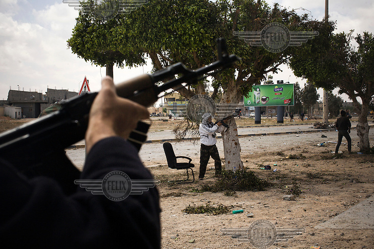 Rebels stand behind trees as they engage in heavy street fighting with Gaddafi forces in central Misurata. On 17 February 2011 Libya saw the beginnings of a revolution against the 41 year regime of Col Muammar Gaddafi.Hours later Guy Martin was seriously injured in an RPG attack.