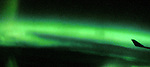 View of a plane wing with the Northern Lights in the background during a flyover Greenland in the spring of 2011.<br />