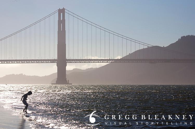 Boy playing under Golden Gate Bridge - San Francisco - California