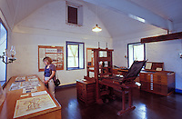 Tourist views exhibits within historical Hale Pai, which is one of the oldest American schools and contains a printing press that created books in Hawaiian